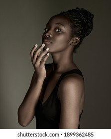 Close-up portrait of a dark-skinned girl on a dark background