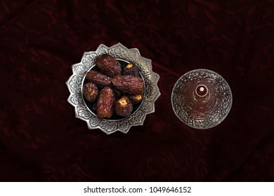 Close-up portrait of dates which are a traditional food to break fast during the holy month of ramadan on a silver serving platter on a red cloth. Dubai, UAE.