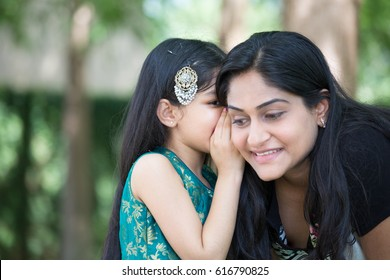 Closeup portrait, daughter whispering secrets in mom's ear, isolated outdoors outside green trees background
