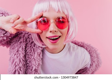 Close-up portrait of debonair girl in trendy peruke. Indoor shot of laughing young woman in sunglasses isolated on pink background.