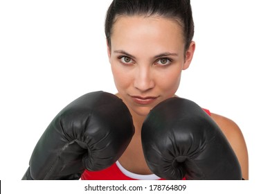 Close-up portrait of a determined female boxer focused on her training over white background