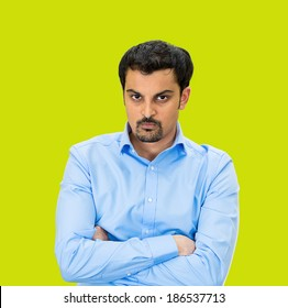 Closeup portrait, displeased, pissed off, angry, grumpy business man, bad attitude, arms crossed, folded, looking at you, isolated green background. Negative human emotion, facial expression, feeling