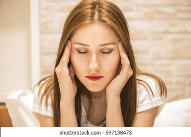 Closeup portrait displeased, pissed off, grumpy, pessimistic, woman with hands on head with bad headache sitting on the bed. Negative human emotions face expression feelings life perception