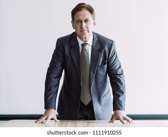 Closeup portrait of dissatisfied middle-aged business man looking at camera and leaning on table with whiteboard in background