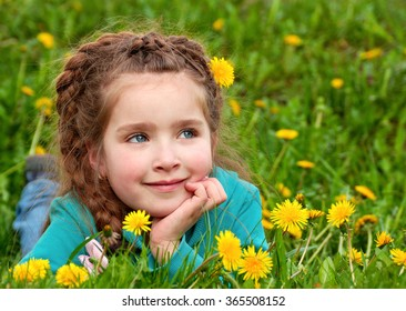 close-up portrait of dreaming beautiful little girl in green grass with yellow dandelions