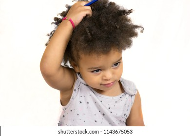 Close-up portrait of dreamy african american little girl touching amazing curly hair. Adorable baby sitting and posing at studio. Isolated on white background