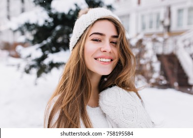 Close-up portrait of dreamy long-haired girl with beautiful eyes spending time outdoor in frosty morning. Photo of ecstatic caucasian female model in white knitted hat enjoying winter time.