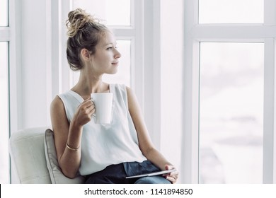 Closeup portrait of dreamy young beautiful fair-haired woman drinking tea, using tablet and looking through window on loggia at home
