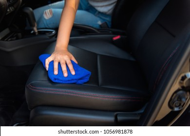 Close-up portrait of a driver woman cleaning her car seat with microfiber towel.