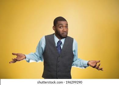 Closeup portrait dumb looking, clueless business man, arms out asking why, what's problem, so what, I don't know, isolated yellow background. Negative human emotion facial expression, life perception