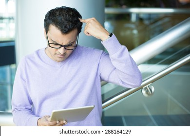 Closeup portrait, dumbfounded, flabbergasted man in black eyeglasses and purple sweater, scratching head, looking at tablet, isolated indoors office background