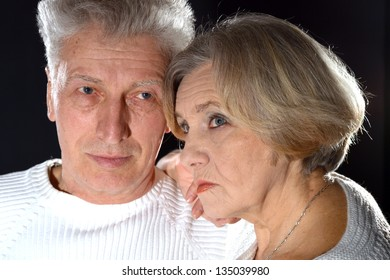 close-up portrait of an elderly couple embracing on a black background
