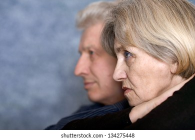 close-up portrait of an elderly couple on a gray background