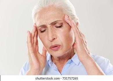 Close-up portrait of elderly lady with headache isolated on white background