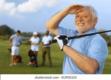 Closeup portrait of elderly male golfer, holding golf club, following shot.
