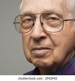 Close-up portrait of elderly man in glasses.