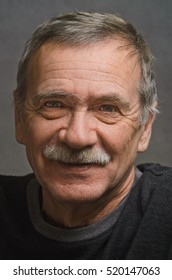 Close-up: portrait of an elderly man looking at the camera and very good smiles