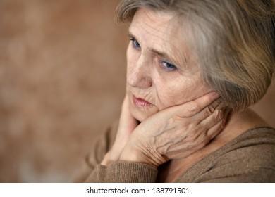close-up portrait of an elderly woman in a beige sweater