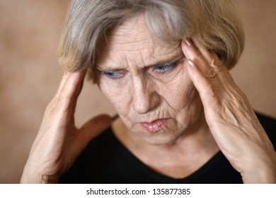 close-up portrait of an elderly woman with a headache on a beige background