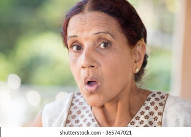 Closeup portrait, elderly woman in white dress taken aback, blown away, by what she sees or hears, isolated outdoors outside background with green trees