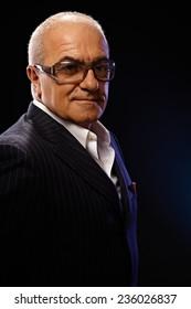 Closeup portrait of elegant mature man over black background.
