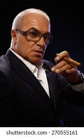 Closeup portrait of elegant mature man smoking cigar, looking at camera.