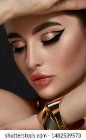 close-up portrait of elegant woman make-up with golden jewelry and black arrows, glamorous style, luxury lifestyle with brunette