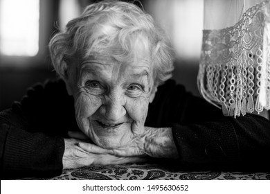 Close-up portrait of emotional elderly woman in his home. Black-and-white photo.