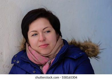 Close-up portrait european brunette girl with short hair in a blue jacket and scarf near white wall looks to the side, waiting