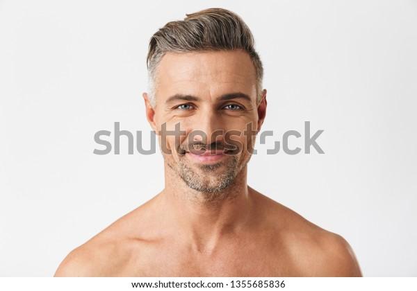 Nahaufnahme eines europäischen halb nackten Mannes der 30er mit brillantem Lächeln bei der Kamera einzeln auf weißem Hintergrund