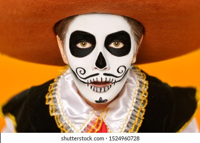Close-up portrait of excited emotional boy with sugar skull makeup looking at the camera. Bright yellow background. Halloween. Dia de los muertos. Day of the dead.