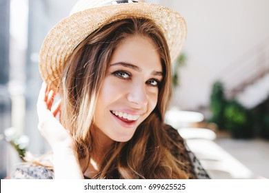 Close-up portrait of excited girl with pale skin and big gray eyes happy posing on blur background. Indoor photo of ecstatic long-haired lady wearing straw hat laughing to camera.