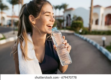 Closeup portrait excited happy young woman smiling with closed eyes to sun with bottle of water. Attractive sportswoman, enjoying summer, training, outwork, happiness