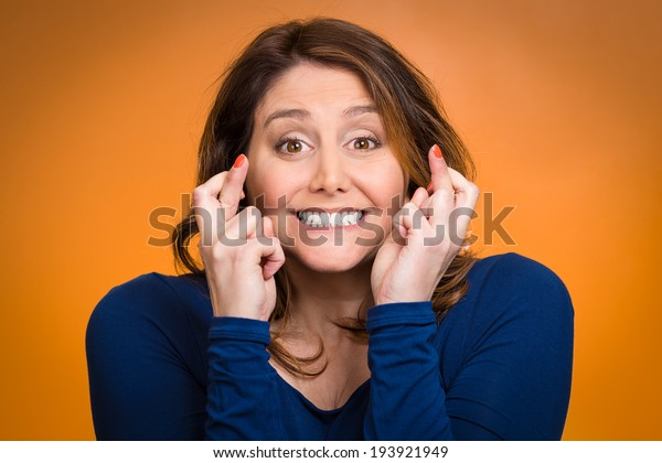 Closeup portrait excited, smiling, hopeful beautiful woman, mother crossing her fingers hoping, asking for best isolated orange background. Human face expressions, emotions, feeling, attitude reaction