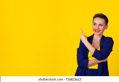 Closeup portrait excited young happy, funny woman presenting the yellow copyspace on her right with index finger pointing, looking to side isolated yellow background. Positive  facial expression sign