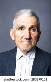 Closeup portrait of expressive old man  over gray background