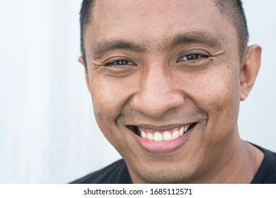 A closeup portrait of a face of an Asian Indonesian male model who smiles with his mouth wide open. he looks happy. Picture is on white background
