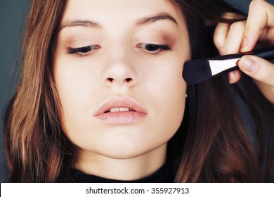 Close-up portrait . In the face of the girl model, make-up artist on the basis of tone is a special brush. Face Care , bb and cc cream. Nude make up