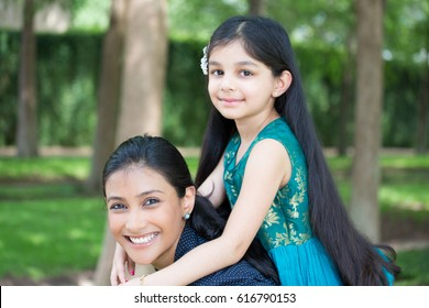 Closeup portrait, family having fun hanging out, girl sitting on top woman shoulders, isolated green trees outdoors background