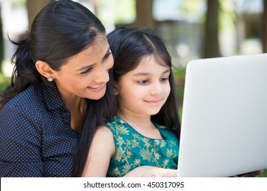 Closeup portrait, family looking at silver laptop together, isolated outdoors outside background