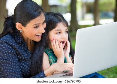 Closeup portrait, family looking at silver laptop together, wide open mouth shocked by what they see, isolated outdoors outside background