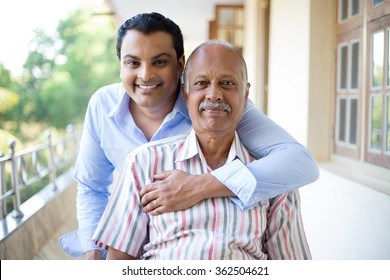 Closeup portrait, family, young man in blue shirt holding older man in striped shirt from behind, happy isolated on outdoors outside balcony background