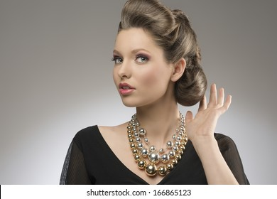 close-up portrait of fashion pretty girl with brown elegant hair-style and bright big necklace.
