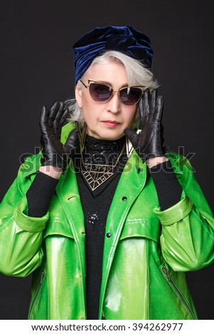 1f46874815f0 Close-up portrait of fashionable old woman in sunglasses wearing expensive  leather gloves. Old
