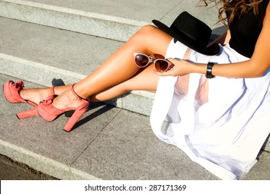 close-up portrait of fashionable and  trendy young  lady,posing at the city,glamour accessories sunglasses,summer shoes,perfect legs,summer collection of shoes,stylish sandals,summer dress code