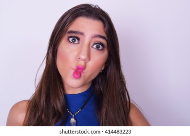 Closeup portrait of fashionable young woman wearing stylish urban clothes, doing fun expression. Fashion studio portrait over grey backgroung.