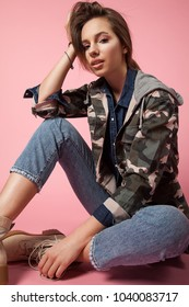 Close-up portrait fashionalble woman  on a pink background in jeans, military jacket and in rough shoes