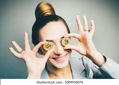 close-up portrait fashioned woman in business suit having fun with two bitcoin coins. smile and happy.