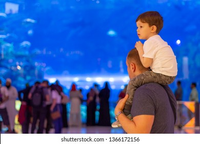 Close-up portrait of a father carrying his son on the shoulders at aquarium. Portrait of happy father giving son piggyback ride on his shoulders and looking up.
