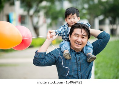 Close-up portrait of a father carrying his son on the shoulders with colorful balloons